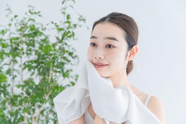 洗顔後に肌をタオルで拭く女性